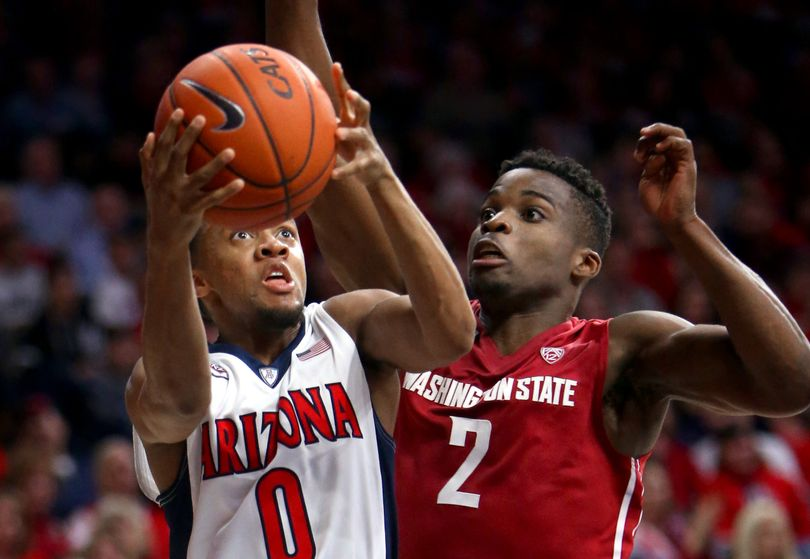 Arizona guard Parker Jackson-Cartwright, left, gets by Washington State guard Ike Iroegbu during an NCAA college basketball game Saturday, Jan. 16, 2016. Iroegbu led the Cougars with 13 points in the Wildcats' 90-66 win in Tucson, Ariz. (Kelly Presnell / AP)