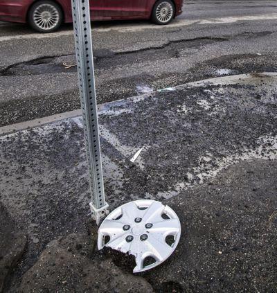 A broken hubcap sits alongside broken pavement at the corner of Freya Street and Congress Avenue, Feb. 17, 2017, in Spokane, Wash. (Dan Pelle / The Spokesman-Review)