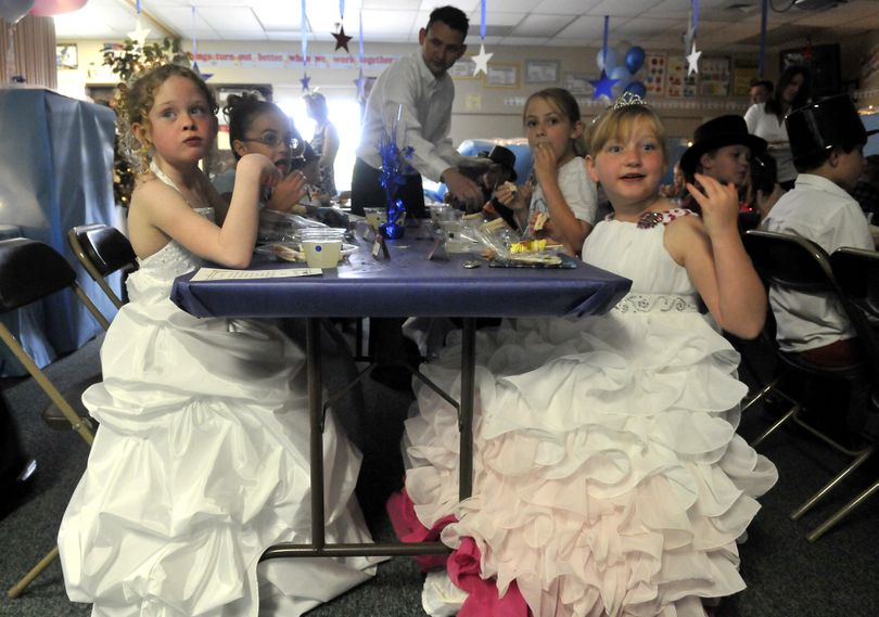 Third-graders Audrina Gainey, left, and Stephanie Sawchuk, right, wear ball gowns and munch on a lunch served by parents and teachers May 24, at Sunrise Elementary. The event, called the Fairy Tale Ball, was a time to dress up and practice proper dining etiquette. (Jesse Tinsley)