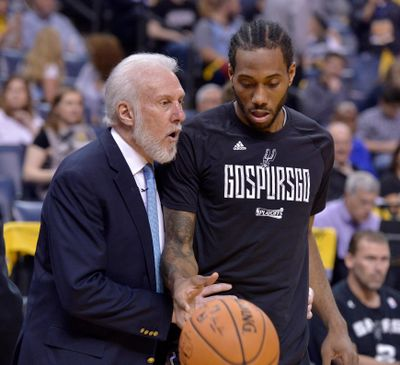 San Antonio Spurs head coach Gregg Popovich, left, talks April 22, 2017, with San Antonio Spurs forward Kawhi Leonard during the second half of Game 4 in an NBA basketball first-round playoff series against the Memphis Grizzlies, in Memphis, Tenn. (Brandon Dill / Associated Press)
