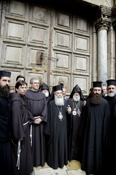 Greek Orthodox Patriarch of the Holy Land, Theophilos III, center, stands outside the closed doors of the Church of the Holy Sepulchre, traditionally believed by many Christians to be the site of the crucifixion and burial of Jesus Christ, in Jerusalem, Sunday, Feb. 25, 2018. (Mahmoud Illean / Associated Press)