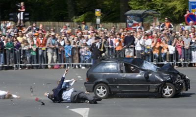 A spectator tumbles to the ground in Apeldoorn, Netherlands, on Thursday after being hit by a car speeding toward a bus carrying Queen Beatrix and her family. Five people were killed.  (Associated Press / The Spokesman-Review)
