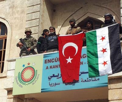 A Turkish and a Turkey-backed Free Syrian Army soldier wave Turkish and FSA flags in the city center of Afrin, northwestern Syria, early Sunday, March 18, 2018. (Hasan Kirmizitas / Associated Press)