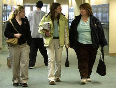 Shiri Howell, 17, middle, and her mom Angie, right, discuss where they will meet when Howell is done with her classes while Katlyn Laughlin, 18, left, walks with Howell to her next class.   (Liz-Anne Kishimoto / The Spokesman-Review)
