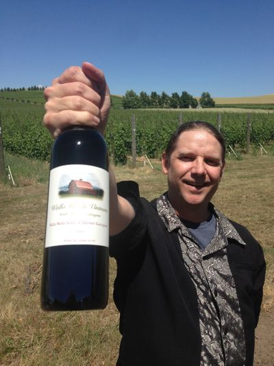 William vonMetzger, winemaker for Walla Walla Vintners, holds a bottle of his award-winning 2012 cabernet sauvignon at the winery's estate vineyard east of Walla Walla. (Andy Perdue)