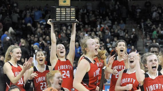 Liberty's Maisie Burnham hoists up the State 2B trophy after the Lancers defeated La Conner 52-45 at the Spokane Arena on Saturday, March 7, 2020. (Kathy Plonka / The Spokesman-Review)