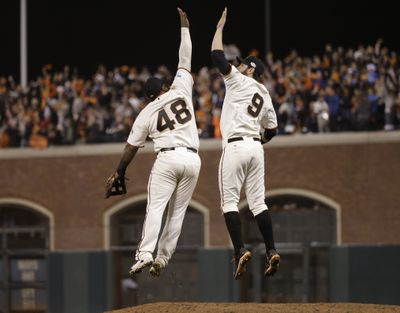San Francisco Giants Pablo Sandoval, left, leaps up to high five Brandon Belt after defeating the Kansas City Royals 11-4 in Game 4 of baseball's World Series Saturday in San Francisco. (Associated Press)