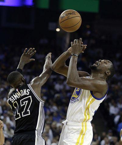 San Antonio Spurs' Jonathon Simmons, left, blocks the shot by Golden State Warriors' Kevin Durant, right. (Ben Margot / Associated Press)