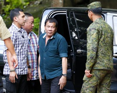 Philippine President Rodrigo Duterte, center, arrives to address troops who are battling Muslim militants who lay siege in Marawi city during his visit to the 2nd Mechanized Infantry Brigade Friday, May 26, 2017 on the outskirts of Iligan city in southern Philippines. Duterte told the troops fighting Muslim militants for the control of southern Marawi city to use martial law powers to defeat the Islamic State group-linked extremists. (Bullit Marquez / Associated Press)