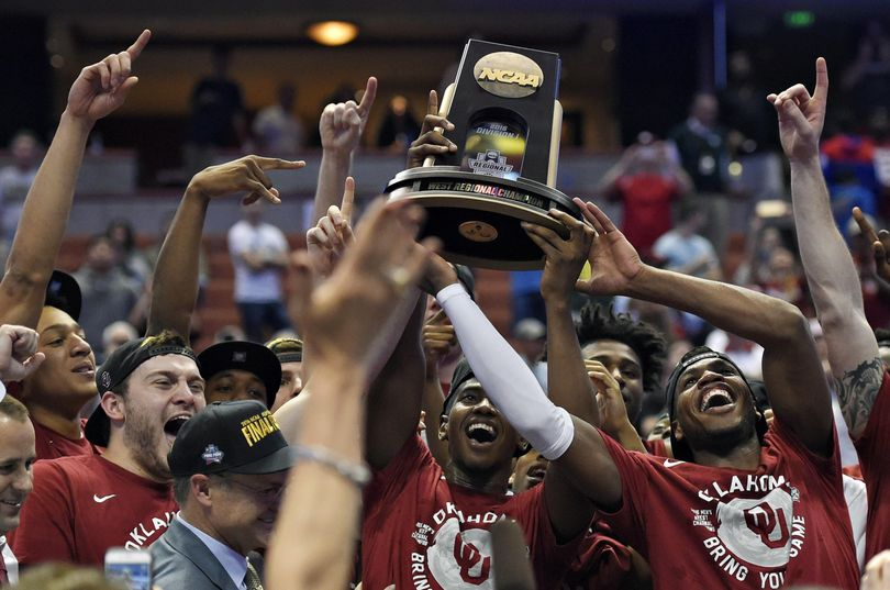 Oklahoma guard Buddy Hield holds the trophy as he and his teammates celebrate their win over Oregon. (Mark J. Terrill / Associated Press)