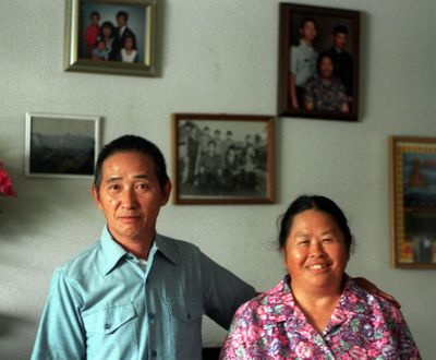 When this photo was taken in June 1997, Ka Toua and Mee Yang Xiong had been in the United States for 15 years. Family photos decorated the wall in the living room of their North Side home.  (Shawn Jacobson/The Spokesman-Review)