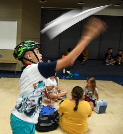 Bemiss Elementary School student Robert Gonzalez launches a paper plane he folded during The SHOP after-school program on Friday, Aug. 30. (Dan Pelle / The Spokesman-Review)
