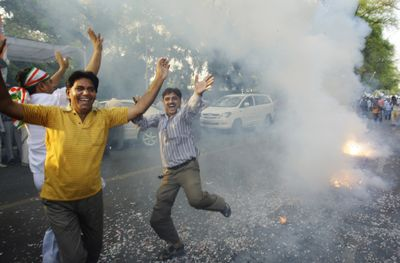 A Congress party supporter dances in celebration as fireworks go off outside the Congress party President Sonia Gandhi's residence in New Delhi, India, Saturday.  (Associated Press / The Spokesman-Review)