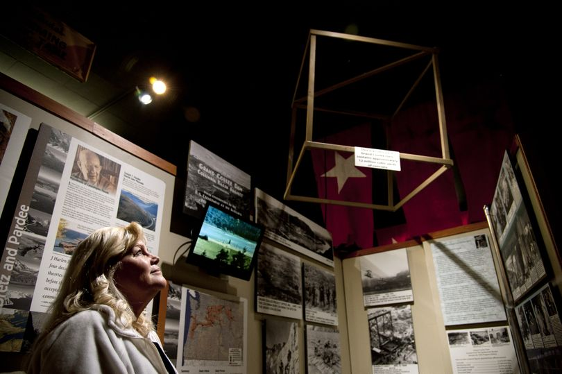 Jayne Singleton, director of the Spokane Valley Heritage Museum, is ready to open the Grand Coulee Dam and Ice Floods exhibit. The box hanging from the ceiling denotes one cubic yard. Grand Coulee Dam contains around 12 million cubic yards of concrete. (Dan Pelle)
