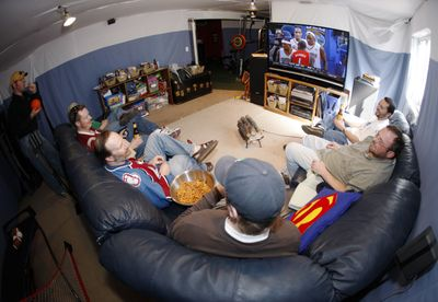 From right, Greg Nuccio, John Otterson, Tom Bruce, Joe Stone, Eirik Thune-Larsen and Fred Wilson sit on a pair of couches to watch college basketball conference finals on a big-screen television while Bill Reeves, back left, looks on in Stone's basement turned into a man cave in Thornton, Colo., last week.  (Associated Press / The Spokesman-Review)