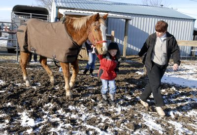 Mozelle Callihan leads 5-year old Jameson Wasson and Dusty, the 27-year-old horse, into the pasture behind her house  Dec. 16. (File / The Spokesman-Review)