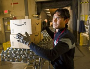 An Amazon.com employee grabs boxes to be loaded onto a truck at the company's Fernley, Nev., warehouse.  (File Associated Press / The Spokesman-Review)