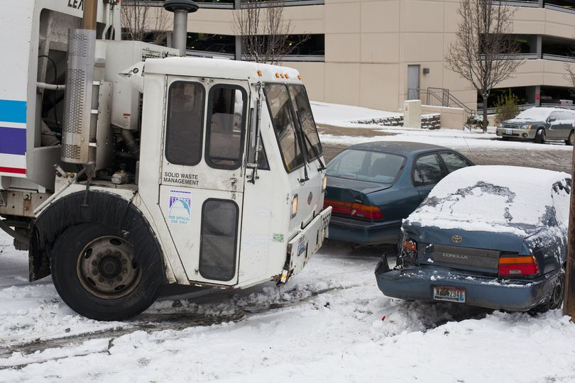 The chains and parking brake of a Spokane garbage truck snapped during the Thursday morning commute. The truck collided with multiple cars on its way down Howard Street near Sixth Avenue.  (Nicole Hensley)