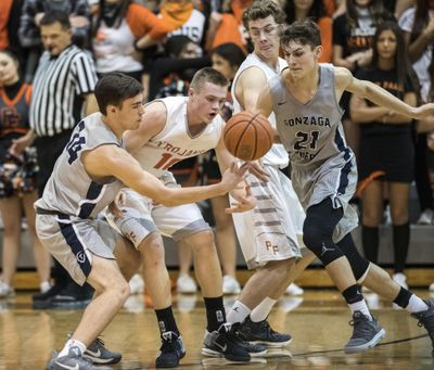 Gonzaga Prep's Carter Sonneborn, left,  battles  Post Falls for a loose ball on  Dec. 7, 2017, in Post Falls. (Dan Pelle / The Spokesman-Review)