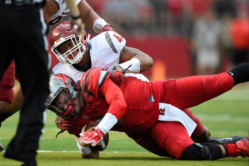 Rutgers quarterback Chris Laviano is greeted by Washington State linebacker Logan Tago during the Cougars 37-34 win last September. (Rich Kane / Associated Press)