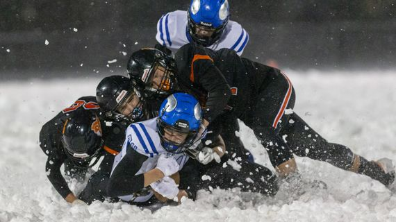 Coeur d'Alene wide receiver Cameren Cope plows through a group of Post Falls defenders during Friday's key matchup in Post Falls.  (Cheryl Nichols/For The Spokesman-Review)
