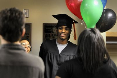 Marcus Fletcher, center, celebrates with family and friends after receiving his high school diploma Thursday night at the Spokane Public Schools Administration Building boardroom. Five young men from Rogers and LC got their diplomas midyear.  (Jesse Tinsley / The Spokesman-Review)