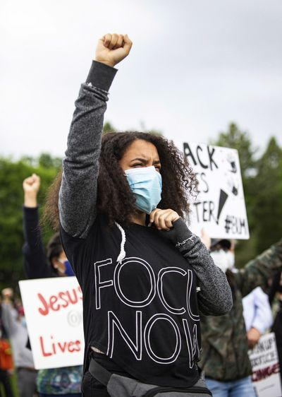 Mya Montgomery gives the Black Power sign as she peacefully protests in Riverfront Park's Lilac Bowl in Spokane, Wash. on Sunday, June 7, 2020. The protest was held to remember Breonna Taylor, an African American woman was fatally shot in Louisville, Ky., by police in her own home in March, as well as to call for change against systemic racism and police brutality. (Libby Kamrowski/The Spokesman-Review via AP) ORG XMIT: WASPO704  (Libby Kamrowski)