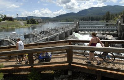 Cyclists scope  the North Channel Dam at Falls Park on the Spokane River, part of the Post Falls Dam. The park is in line for a facelift. (J. BART RAYNIAK / The Spokesman-Review)
