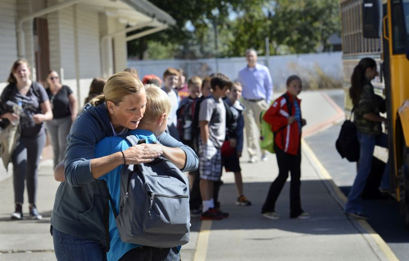 Angie Bordwell, a seventh-grade teacher at East Farms STEAM Magnet School, hugs her student, Dmitriy Cherkashin, before he boards a bus back to East Valley Middle School on Wednesday in Spokane Valley. (PHOTOS BY DAN PELLE)