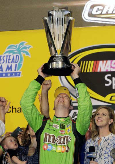 Kyle Busch raises his trophy after winning the NASCAR Sprint Cup Series auto race and the season title Sunday at Homestead-Miami Speedway in Homestead, Fla.
