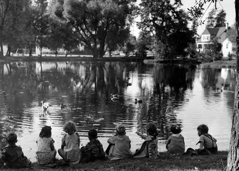 Indian summer has touched its magic wand to Manito park, clothing the ground, trees and shrubs in a riot of fall colors. Taking in the beauty of the scene and visiting the wild ducks on the park pond are visitors from the Lincoln child care center. Oct. 17, 1943.  (Photo Archive/spokesman-review)