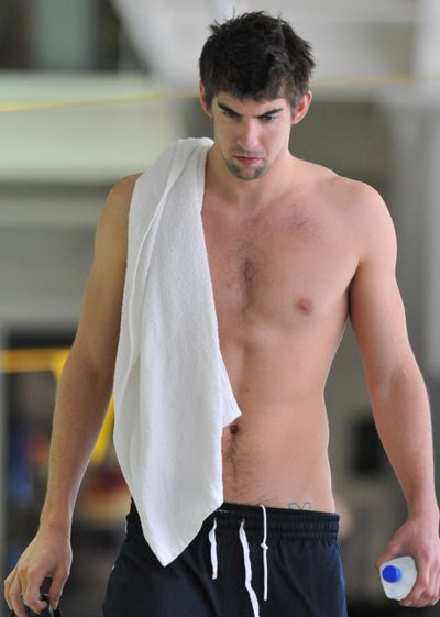Olympic gold medalist Michael Phelps walks toward reporters to answer questions before training in February. The swimming superstar was suspended for three months and had his training stipend revoked by USA Swimming, after a photo of him smoking marijuana appeared in a British  tabloid. (Associated Press / The Spokesman-Review)