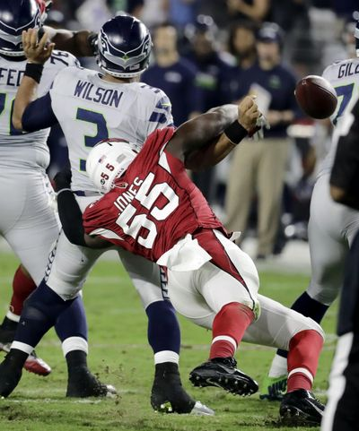 Seahawks quarterback Russell Wilson has the football knocked loose by Cardinals linebacker Chandler Jones (55). (Rick Scuteri / Associated Press)