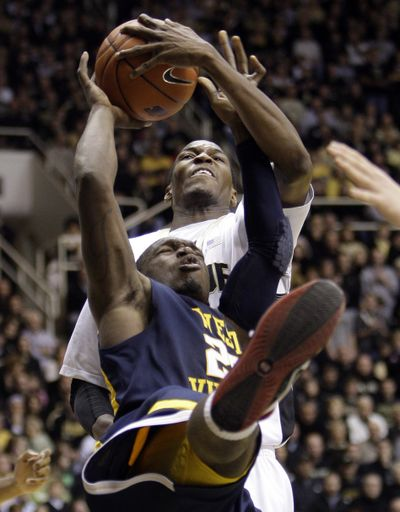 Purdue's JaJuan Johnson, top, blocks the shot of West Virginia's Darryl Bryant during No. 4 Purdue's 77-62 home win.  (Associated Press)