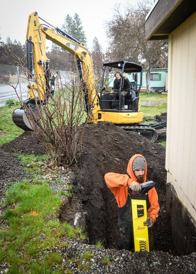 The Pinecroft Mobile Home Park (which has been under a boil water order since last summer) finally got the go ahead to install a new water system. Colville Construction's Cody Baker, front and Dennis Barton, on the excavator, search for a four-inch water line next to the pump house, Tuesday, March 31, 2020, in Spokane Valley, Wash. (Dan Pelle / The Spokesman-Review)