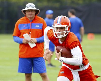 Florida quarterback Feleipe Franks (13) runs with the ball as head coach Dan Mullen watches during an NCAA college football practice in Gainesville, Fla., Friday, July 26, 2019. (Brad McClenny / Gainesville Sun via AP)