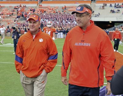 In this Sept. 17, 2011 photo, then-offensive coordinators Chad Morris, left, of Clemson, and Gus Malzahn, right, of Auburn, walk together on the field at Memorial Stadium before an NCAA college football game, in Clemson, S.C. Morris is now the head coach at Arkansas. Malzahn is the head coach at Auburn. The two chat each week – except when they play each other. (Mark Crammer / Independent-Mail via AP)