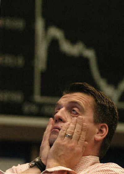 A stock trader reacts in front of the German Stock Index displayed at the stock exchange in Frankfurt, Germany.  (Associated Press / The Spokesman-Review)