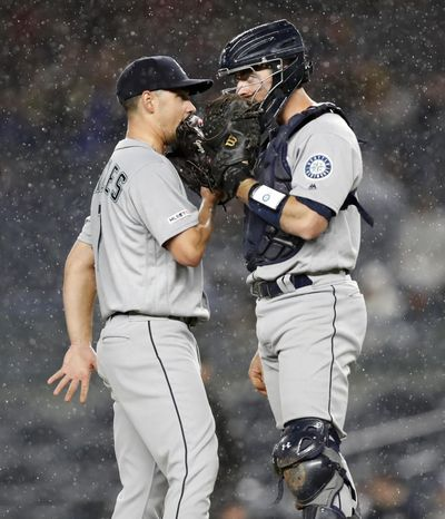 Mariners starting pitcher Marco Gonzales, left, talks to catcher Tom Murphy as rain falls during the sixth inning Tuesday, May 7, 2019, at Yankee Stadium in New York. (Kathy Willens / AP)