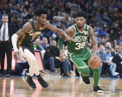 Boston Celtics guard Marcus Smart drives past Oklahoma City Thunder guard Shai Gilgeous-Alexander during the second half on Sunday in Oklahoma City. (Kyle Phillips / AP)