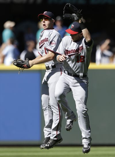 Clete Thomas, left, and Chris Herrmann celebrate after the Twins' win Saturday. (Associated Press)