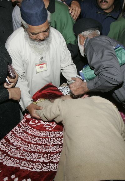 People comfort a family member who mourns over the dead body of slain police officer during a funeral in Lahore, Pakistan, on Tuesday.  (Associated Press / The Spokesman-Review)