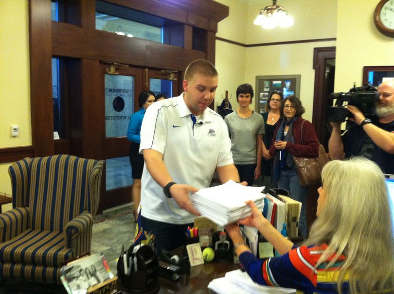 Student leaders, including Bryan Vlok of Boise State University, deliver stacks of letters and petitions opposing guns on campus to Gov. Butch Otter's office on Friday (Betsy Russell)