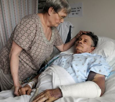 Helen Widener, 69, comforts her husband, Dennis, 66, in Providence Sacred Heart Medical Center on June 29. Dennis, who was injured in a hit-and-run accident while he was riding his bicycle near the corner of Division Street and Garland Avenue, died Wednesday. (Dan Pelle)