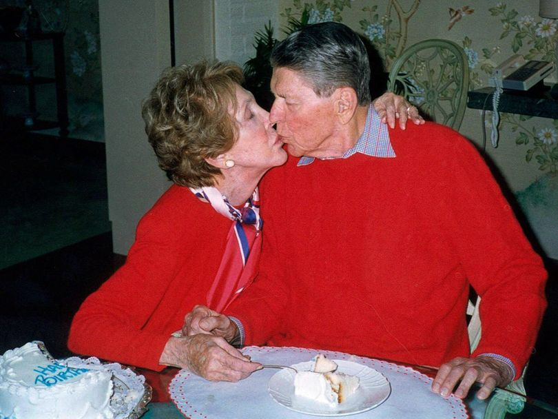 Former President Ronald Reagan, who was a faithful writer of love letters, is kissed by wife Nancy on his 89th birthday in 2000. (Associated Press)