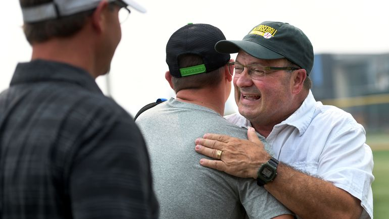 Retired Shadle Park baseball coach Ron Brooks, right, is greeted by Aaron Hancock and Tim Amann, both players from the Highlanders' 1995 team, during his retirement party at Al Jackson Field on Friday.  (Kathy Plonka)