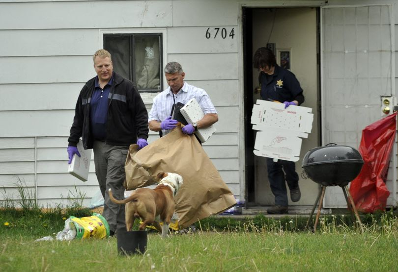 Detective Michael Drapeau (front) and investigators with the Spokane County Sheriff's Office remove evidence from a house at 6704 E. Third Ave. Shane Caleb Smith, 38, was arrested there this afternoon in connection with the homicide of Warren Flinn in Spokane Valley. (Colin Mulvany / The Spokesman-Review)