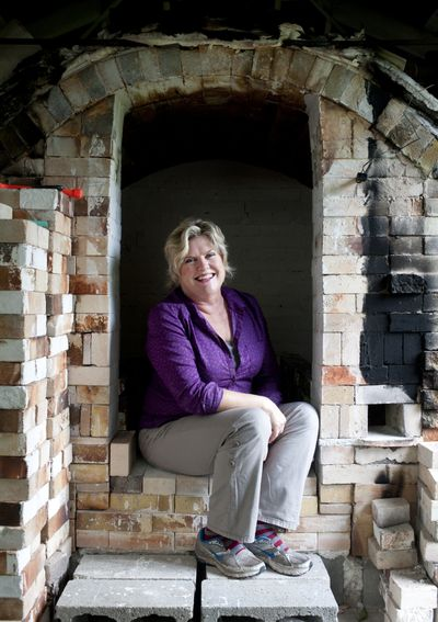Gina Freuen poses for a photo in her kiln on Wednesday, at her home studio in north Spokane. Below, some of Freuen's sculptures are shown. Freuen's studio will be open during the Little Spokane River Artist Studio Tour on Saturday. (Tyler Tjomsland)