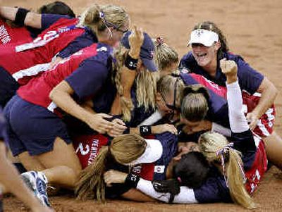 U.S. players pile onto pitcher Lisa Fernandez after their win over Australia in the gold medal game Monday.   (Associated Press / The Spokesman-Review)