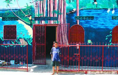 A young student stands in front of Spokane artist Katherine Staib Derrick's finished tropical mural on a school for empoverished children in Granada, Nicaragua.   (The Spokesman-Review)